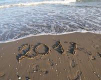 Reusachtige tekst 2017 op het strand en de golven van de oceaan Royalty-vrije Stock Afbeelding
