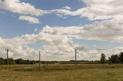 Reusachtige witte wolken in de koude de herfsthemel over groene gebieden, bomen, bossen, stromen Sunnedag Elektrische polen royalty-vrije stock afbeeldingen