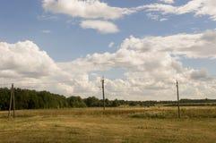 Reusachtige witte wolken in de koude de herfsthemel over groene gebieden, bomen, bossen, stromen Sunnedag Elektrische polen royalty-vrije stock afbeelding