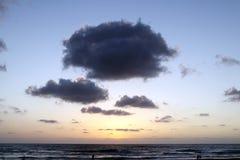 Reusachtige wolken in de stralen van de overzeese zonsondergang royalty-vrije stock foto's