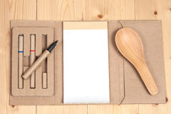 Reuse Note book with pen on a wooden Stock Image