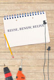 Reuse, renew, relive against tools and notepad on wooden background Stock Photography