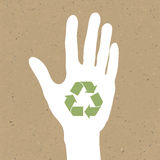 Reuse sign on hand silhouette on recycled paper. Royalty Free Stock Image