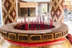 Reuzejoss stokpot met rode wierookstokken stock afbeelding