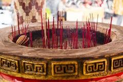 Reuzejoss stokpot met rode wierookstokken stock afbeeldingen