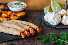 Reuzekoningsgarnalen en selectie van mini Chinese bollen met yoghurt onderdompelende saus royalty-vrije stock afbeelding