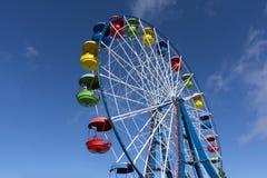 Reuzenrad met gekleurde cabines op de blauwe hemelachtergrond, Zon Stock Foto's