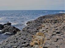 Reuzenverhoogde weg, het trekken stenen De populaire toeristen plaatsen stock foto