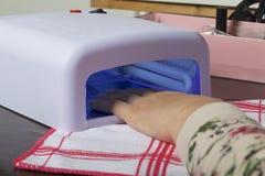 Revêtement de clou avec le gel-vernis Une femme sèche ses clous dans un émetteur à rayonnement ultraviolet Photo stock