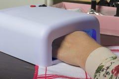 Revêtement de clou avec le gel-vernis Une femme sèche ses clous dans un émetteur à rayonnement ultraviolet Photos stock