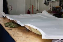 Revêtement de plafonds gris enlevé de la voiture pour accorder et attacher avec le matériel mou gris sur une table dans l'atelier photographie stock libre de droits