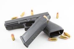 Revólver com balas e grampo no fundo branco Fotografia de Stock