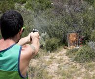 Revólver do tiro do homem em alvos com Shell no ar Fotografia de Stock Royalty Free
