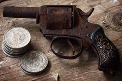 Revólver e moedas mexicanas Imagem de Stock Royalty Free