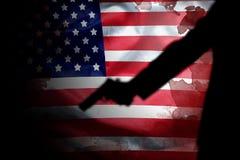 Revólver na mão do atirador com mancha de sangue na bandeira americana imagem de stock