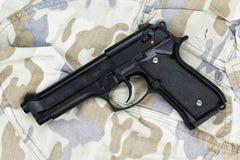 Revólver semiautomático no fundo da camuflagem Fotos de Stock Royalty Free