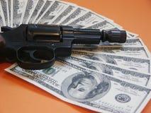 Revólver y dinero Imagenes de archivo