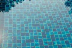 Rev sönder blått bevattnar i simbassäng Arkivfoto
