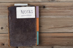 Revamped Old Weathered Brown Notebook on Wooden Planks. Overhead shot of an old, weathered brown notebook updated with colourful new tab dividers along side and Royalty Free Stock Photos