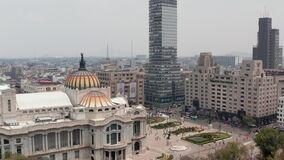 Reveal of city, ascending drone flying around colourful dome with bird sculpture of Palace of fine arts (Palacio de