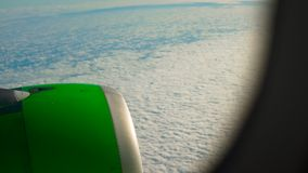 Reveal shot of a a green airplane flying over clouds view from a window on an engine stock footage