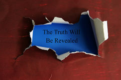 Reveal the truth. Hole torn in a piece of paper with The Truth Will Be Revealed royalty free stock images