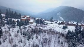 Revealing aerial of inhabited locality in the mountains on winter. Mountain village buildings on snowy hill slopes stock video footage