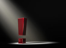 Revealing The Answer. A red exclamation mark in the dark lit by a single, yellow spotlight Stock Photography