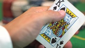 Revealing a blackjack hand of 21 with ace and king spades. Player holding cards with twenty one. Green casino table and betting chips on background stock video