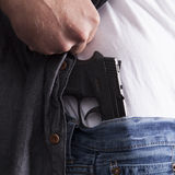Revealing Concealed Firearm. A man reveals a concealed firearm at his side royalty free stock image