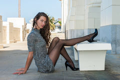 Revealing Long Legs. Pretty brunette in black pantyhose, short dress, and pumps with glimpse of tops with leg crossed over facing right Royalty Free Stock Image