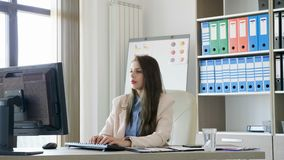 Revealing shot of Businesswoman in office working on PC stock footage
