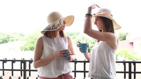 Revealing shot two beautiful and gorgeous woman with large hats on the balcony drinking coffee. Slow motion footage stock video footage