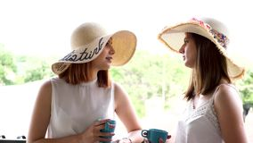 Revealing shot of two beautiful and gorgeous women in large summer hats on the balcony drinking coffee. And talking. Slow motion footage stock video