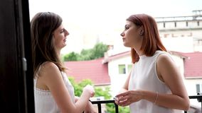 Revealing shot of two beautiful women talking to each other and laughing. Slow motion. Shot on balcony stock video
