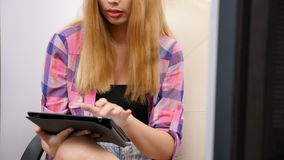Unrecognisable woman at her home office using a digital tablet. Revealing shot of unrecognisable woman at her home office using a digital tablet stock footage