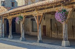 Medieval square with arcade. Revel, Midi Pyrenees, France - August 5, 2017: Arcade and wooden columns in medieval square with flowers Royalty Free Stock Images