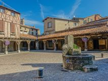 Medieval square with arcade in Revel village. Revel, Midi Pyrenees, France - August 5, 2017: Medieval square with stone fountain and wooden arcades with flowers Royalty Free Stock Image