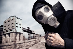 Revelation. Human in gas mask outdoors and industrial factory on a background Stock Photos