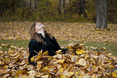Revelling in the Joys of Fall. Girl enjoying fall while sitting in a pile of colorful fall leaves Royalty Free Stock Photos