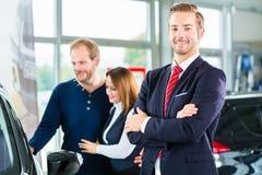 Revendeur, clients et automobile au concessionnaire automobile image libre de droits