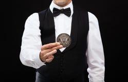 Revendeur tenant la pièce de monnaie de demi-dollar Photographie stock libre de droits