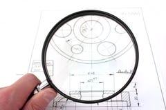 Revendo o desenho técnico. Foco no magnifier. Foto de Stock Royalty Free