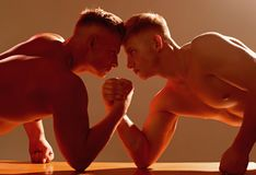 Revenge in sport. Men competitors try to win victory or revenge. Strength skills. Twins men competing till victory. Twins competitors arm wrestling. Stronger royalty free stock photography