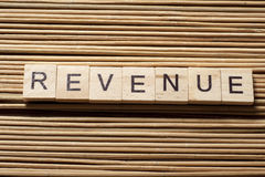 REVENUE word written on wood block at wooden background. Royalty Free Stock Photos