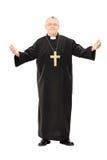 Reverend maduro en capa negra con las manos abiertas Fotografía de archivo libre de regalías