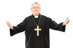 Reverend maduro en capa negra con las manos abiertas Imagen de archivo