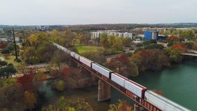 Reverse aerial view of train on Trestle Bridge in Austin Texas. Austin, TX - Circa December, 2017 - A slow forward aerial flyover view of a cargo train traveling stock footage