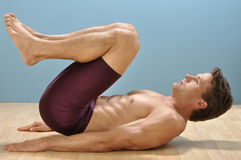 Reverse crunch. Fit muscular shirtless man performs reverse crunch abdominals exercise on floor stock images