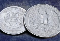 Reverse of the one Russian ruble coin and twenty-five US cents Stock Image